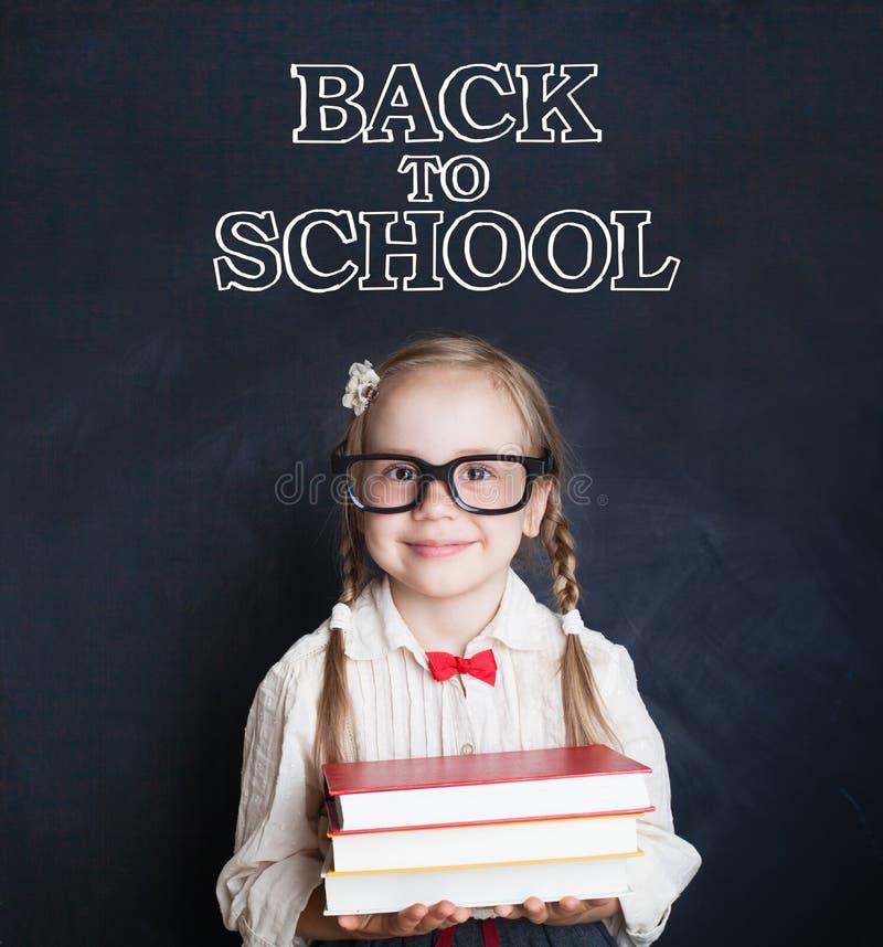 Élève mignon de petite fille tenant la pile des livres et du sourire photo libre de droits