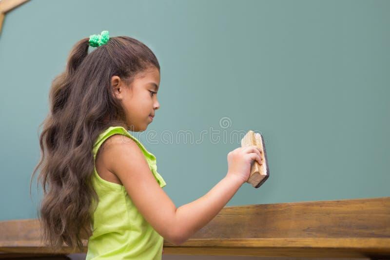 Élève mignon se tenant dans le tableau de saupoudrage de salle de classe photographie stock