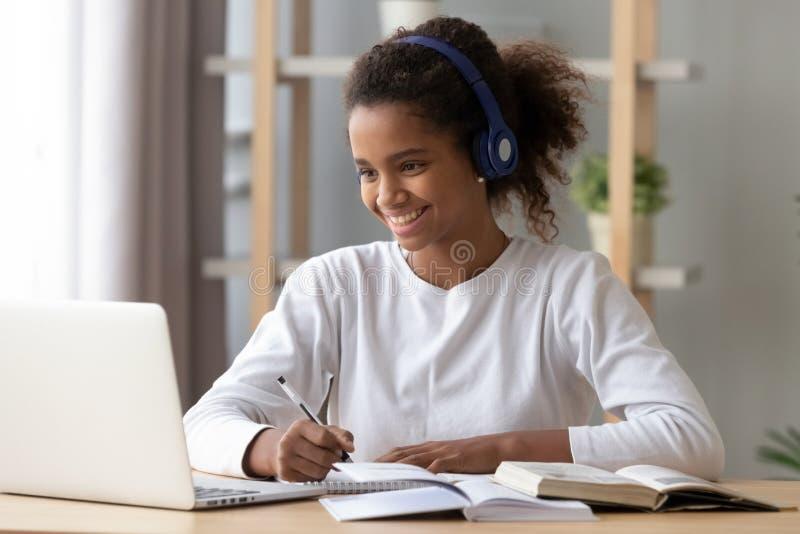 Élève noir heureux dans des écouteurs faisant des devoirs d'école image stock