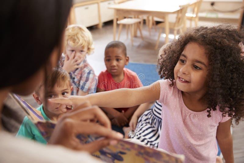 Élèves à l'école de Montessori regardant le livre avec le professeur photographie stock libre de droits