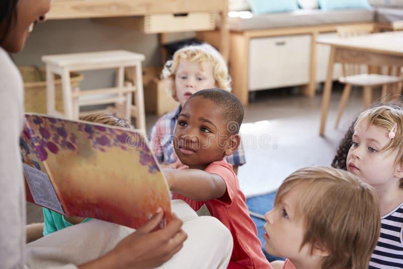 Élèves à l'école de Montessori regardant le livre avec le professeur photos libres de droits