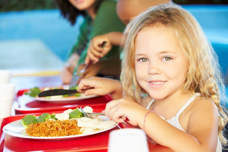 Élèves élémentaires appréciant le déjeuner sain dans le cafétéria images stock