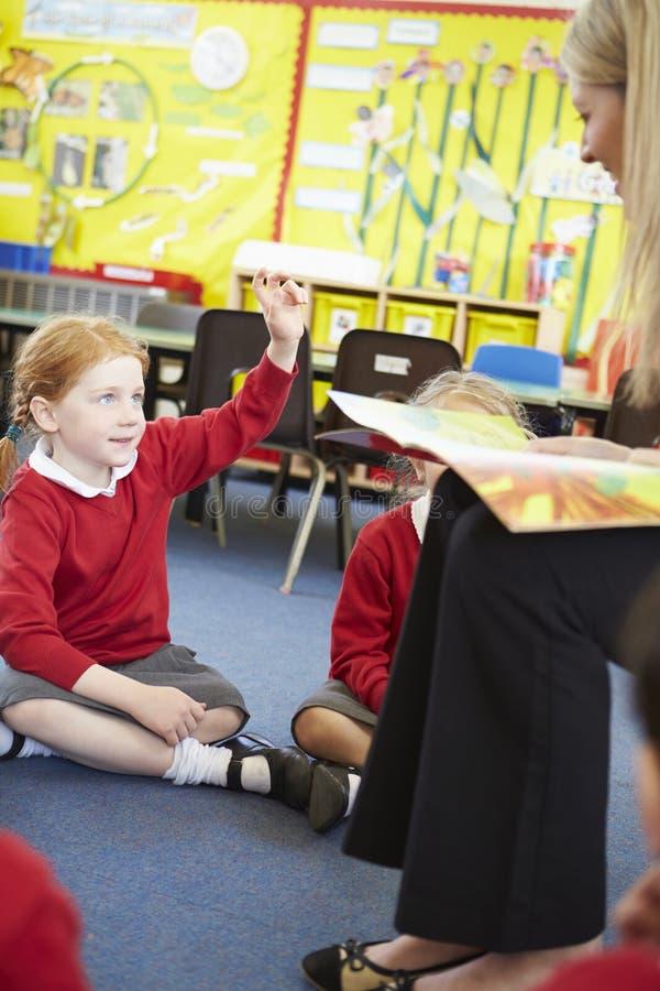 Élèves d'école primaire de Reading Story To de professeur photos libres de droits