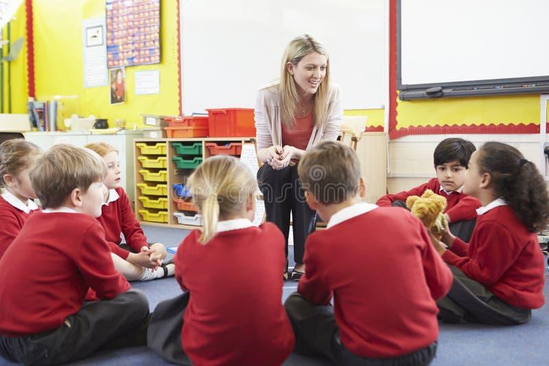 Élèves d'école primaire racontant l'histoire au professeur images stock