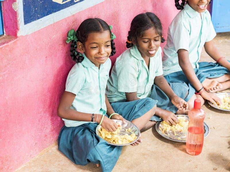Élèves d'adolescentes de filles étant servis le plat de repas du riz dans la cantine scolaire de gouvernement Nourriture malsaine photographie stock