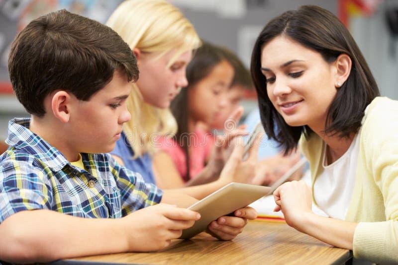 Élèves dans la classe utilisant le comprimé de Digital avec le professeur images stock