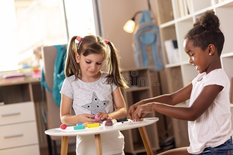 Élèves du cours préparatoire jouant avec de la pâte à modeler colorée photos stock