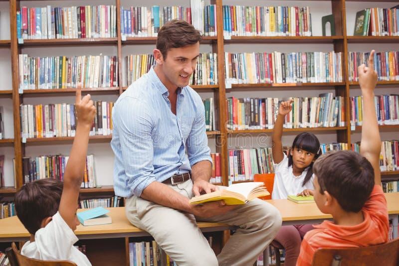 Élèves mignons et professeur ayant la classe dans la bibliothèque photo libre de droits