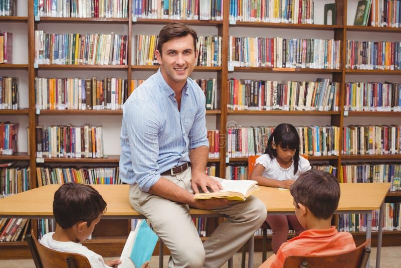 Élèves mignons et professeur ayant la classe dans la bibliothèque images libres de droits
