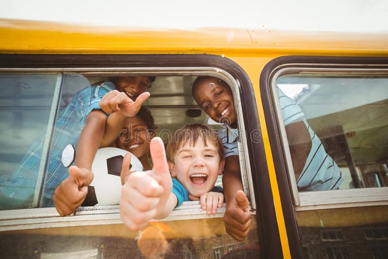 Élèves mignons souriant à l'appareil-photo dans l'autobus scolaire photographie stock