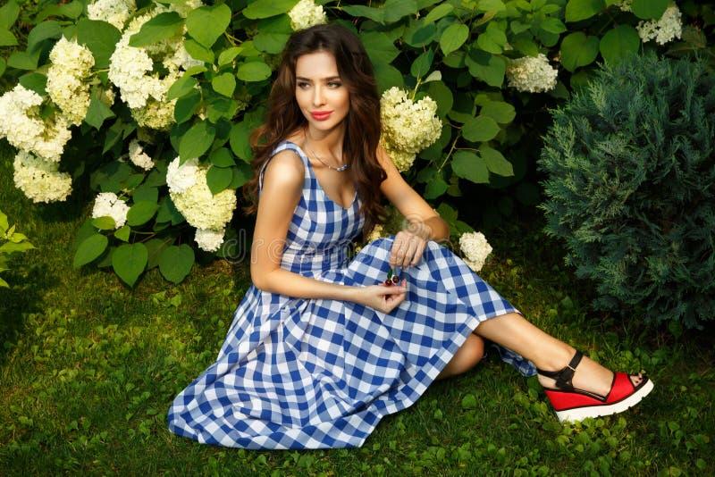 Élégante, assez et la belle jeune dame est se reposante et posante sur la pelouse verte en parc naturel photographie stock