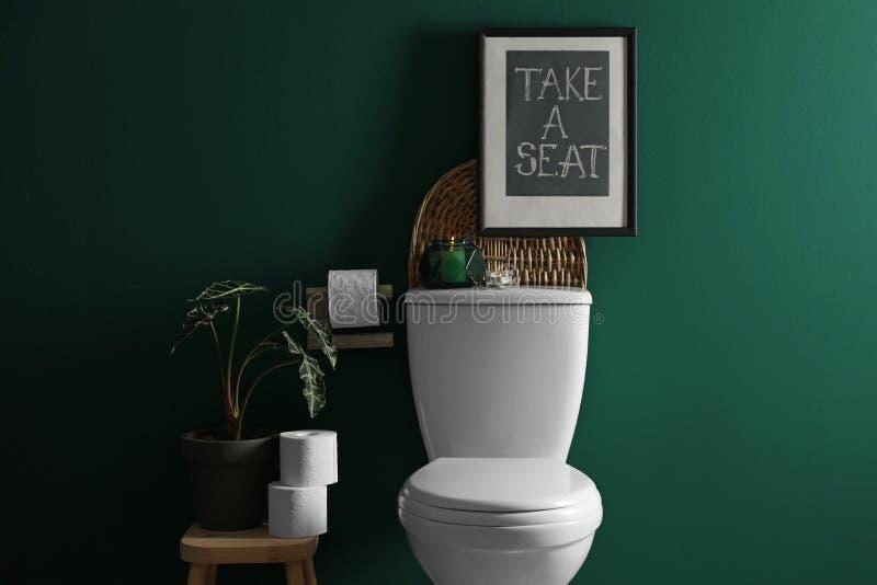 Éléments de décor, petits pains de papier et cuvette des toilettes près de mur vert Salle de bains photographie stock