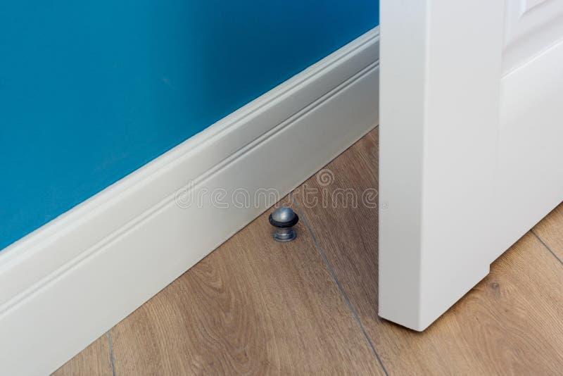 Éléments en gros plan de l'intérieur de l'appartement Bouchon de porte de chrome en métal sur le plancher en stratifié image stock