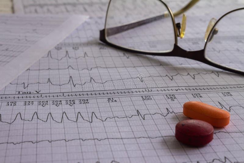 Éléments médicaux sur des bandes d'électrocardiogramme avec le battement de coeur Bureau médical montrant le concept de santé photographie stock libre de droits