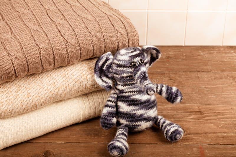 Éléphant tricoté de jouet avec la pile de vêtements tricotés sur en bois photo stock
