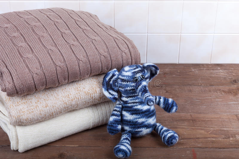 Éléphant tricoté de jouet avec la pile de vêtements tricotés sur en bois photos libres de droits