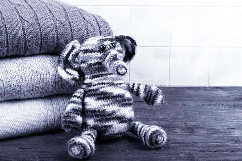 Éléphant tricoté de jouet avec la pile de vêtements tricotés sur en bois photos stock