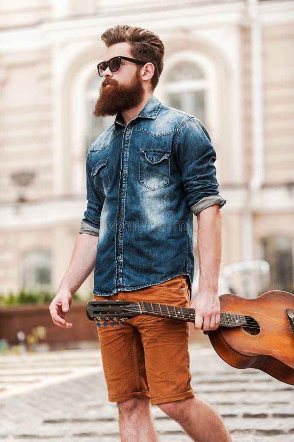 Él nunca está lejos de su guitarra fotos de archivo libres de regalías