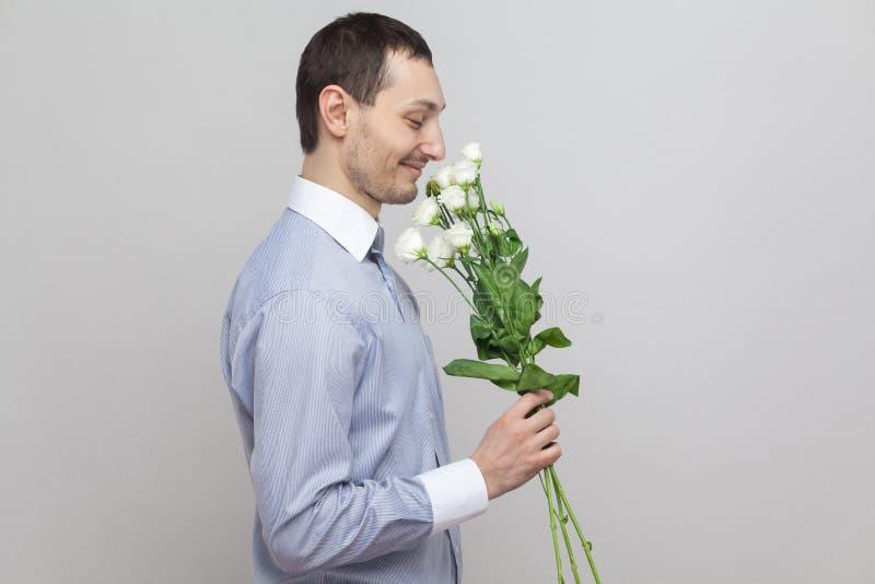 Él quiere dar las flores Retrato de la vista lateral del hombre joven romántico del placer encantador en ramo azul de la tenencia fotos de archivo