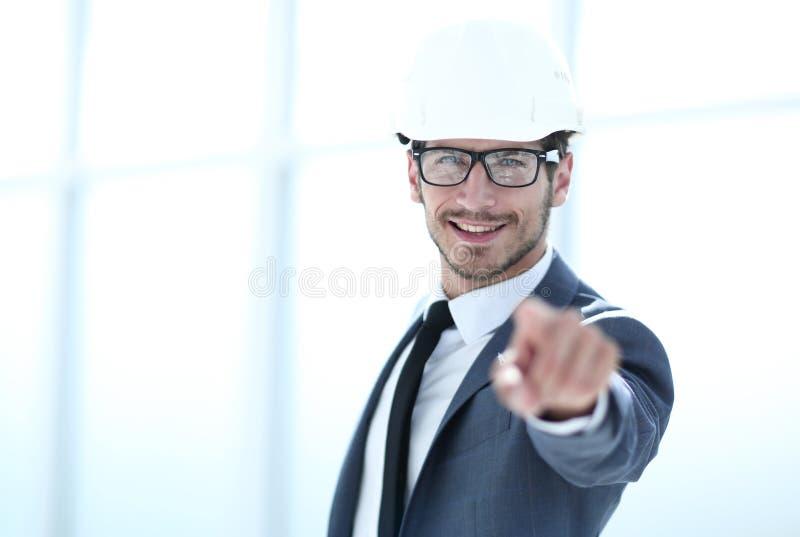 Él sirve en el casco blanco está señalando su finger a la cámara foto de archivo
