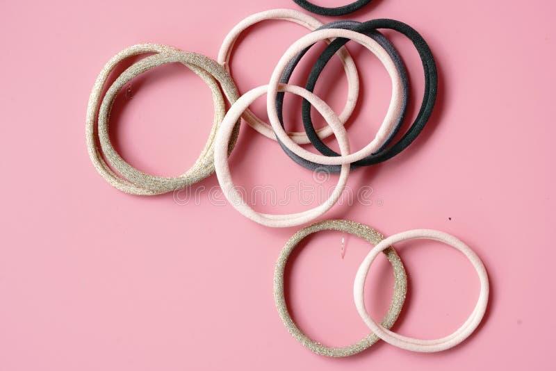 Élastine multicolore pour les cheveux contraignants sur un fond rose image stock