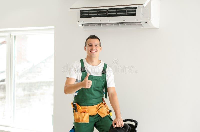 Électricien après la réparation réussie du climatiseur à l'intérieur photo stock