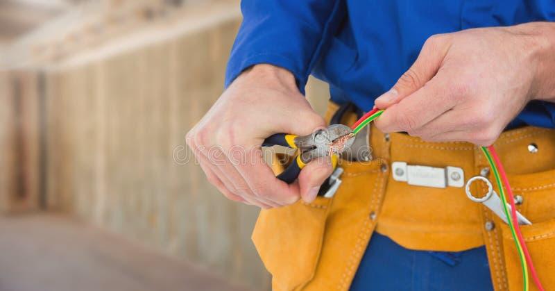 Électricien avec des câbles de fils sur le chantier photo libre de droits