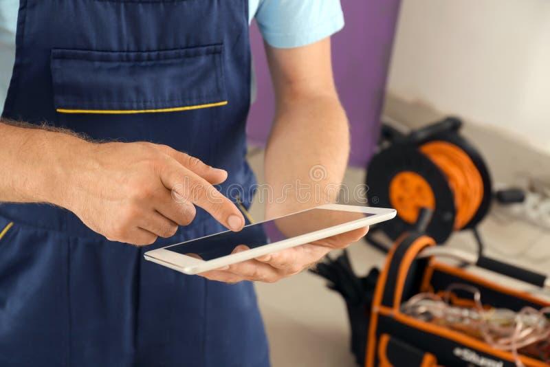 Électricien avec la tablette près du conseil de distribution à l'intérieur photographie stock