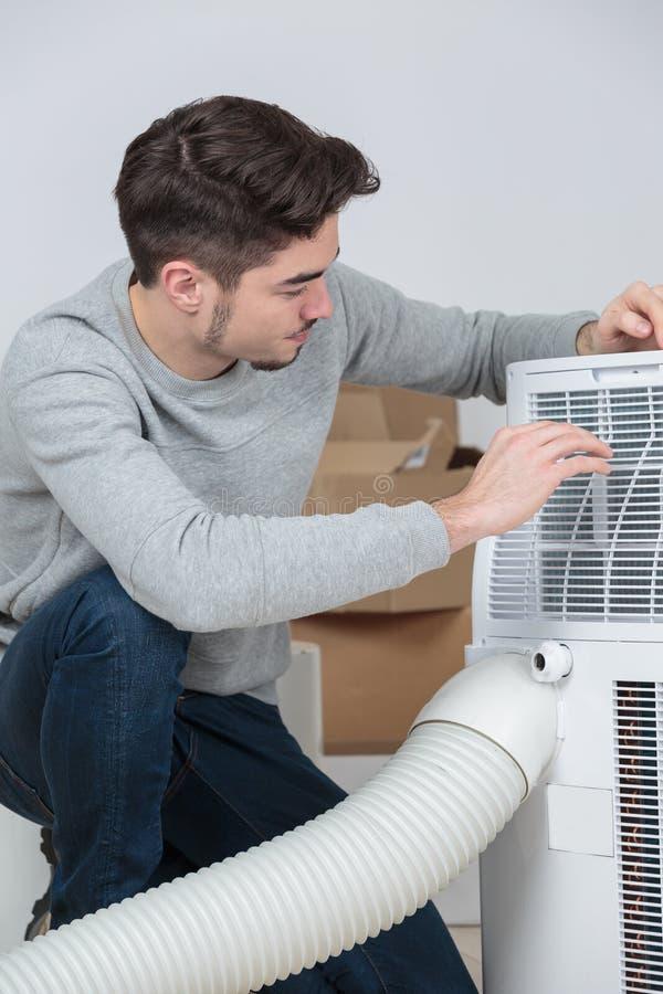 Électricien bel de jeune homme installant la climatisation dans la maison de client images libres de droits