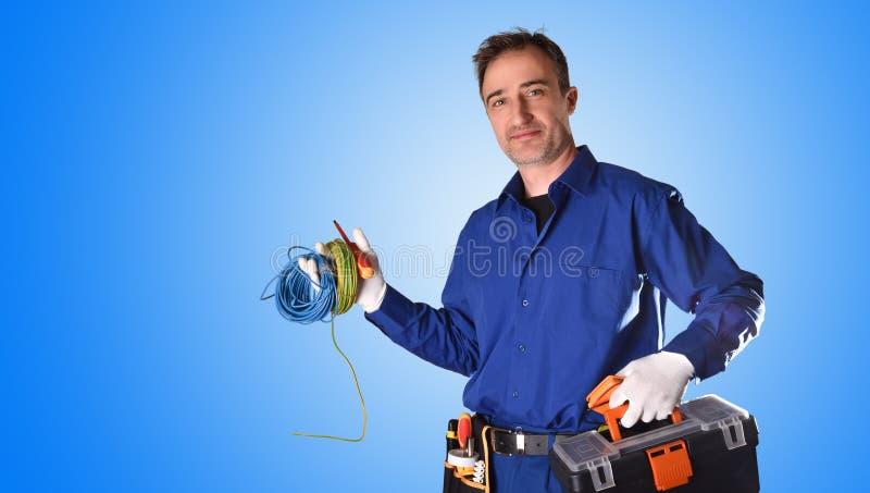 Électricien en uniforme avec les outils et le fond bleu de matériel électrique images stock