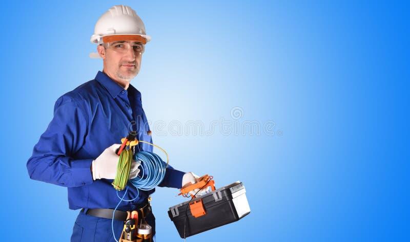 Électricien en uniforme avec les protections de sécurité et le fond d'outils de travail images libres de droits