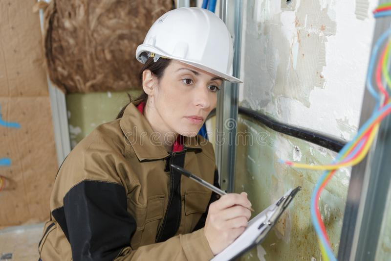 Électricien féminin vérifiant le problème de l'électricité image stock