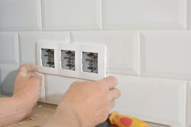 Électricien installant la prise murale photographie stock