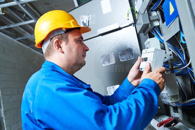 Électricien installant le mètre économiseur d'énergie image stock