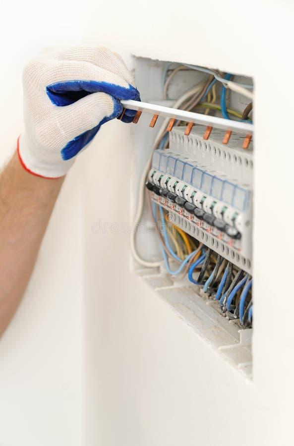 Électricien installant une boîte de fusible électrique images stock