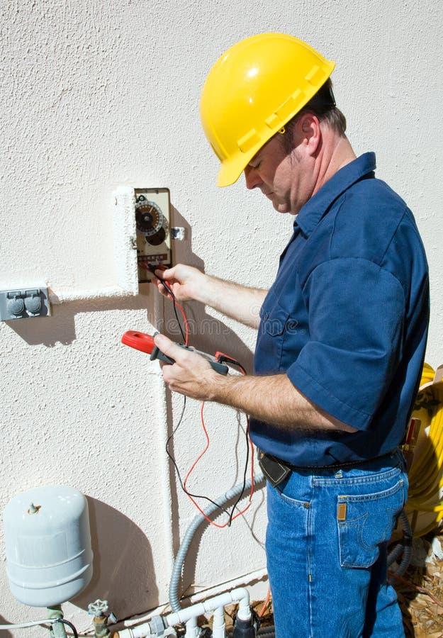 Électricien réparant la pompe d'arroseuse photo stock