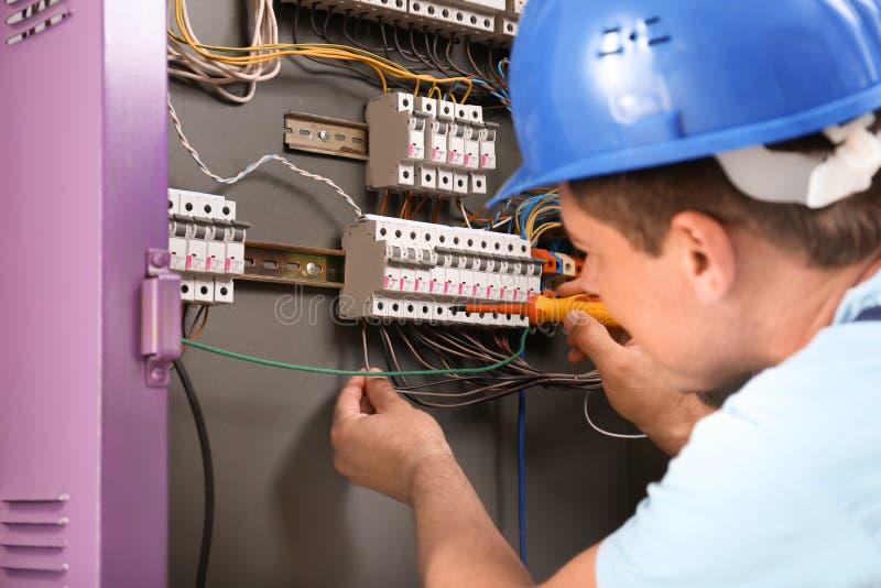 Électricien réparant le conseil de distribution à l'intérieur photographie stock