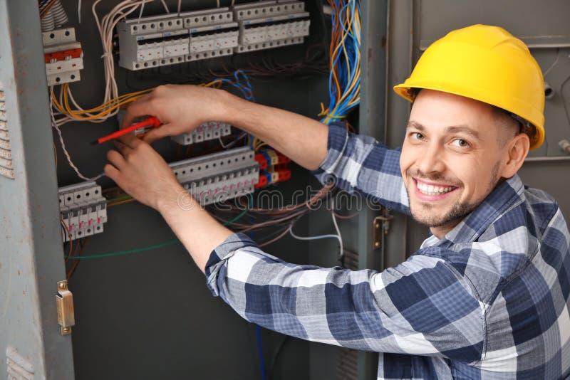 Électricien réparant le conseil de distribution photo stock