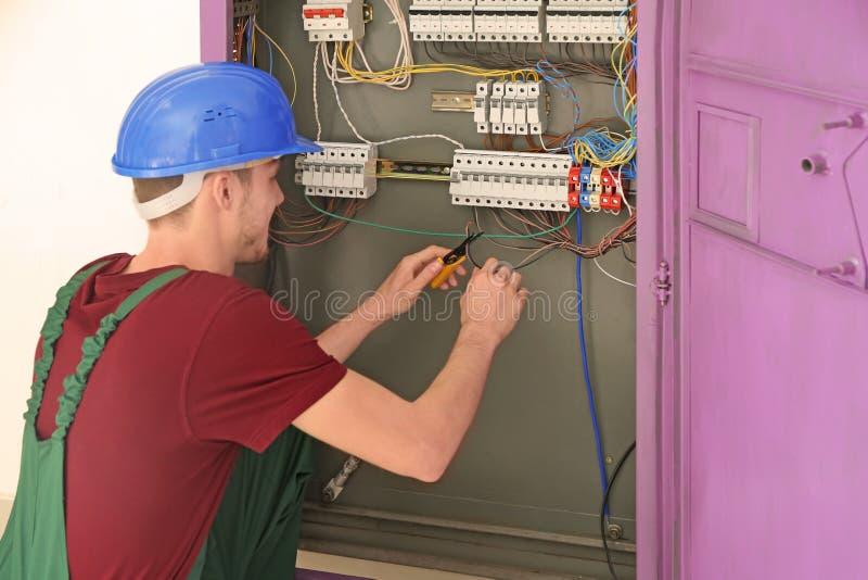 Électricien réparant le conseil de distribution image stock