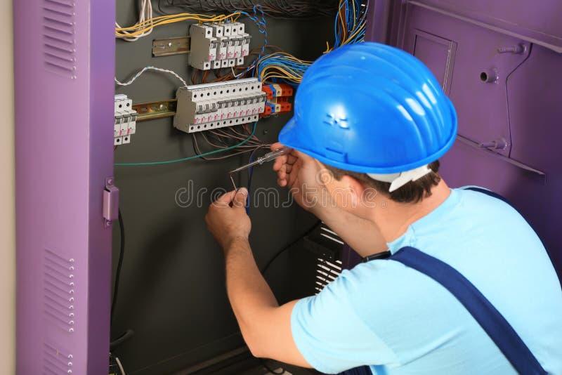 Électricien réparant le conseil de distribution photos stock