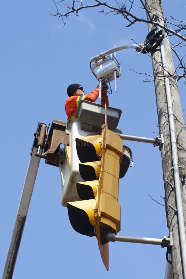 Électricien réparant le feu de signalisation photographie stock libre de droits
