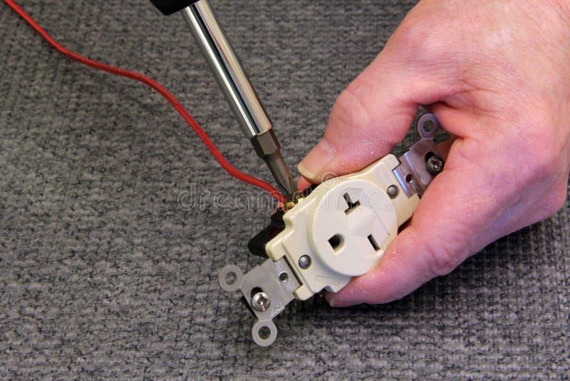 Électricien reliant un fil à un débouché photographie stock