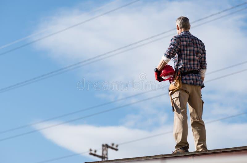 Électricien se tenant sur le dessus de toit photographie stock