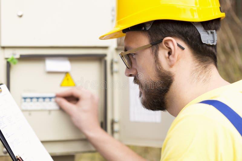 Électricien vérifiant la boîte de fusible photo libre de droits