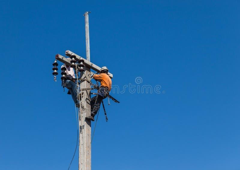 Électriciens montant le travail dans la taille sur le poteau concret de courant électrique photographie stock libre de droits