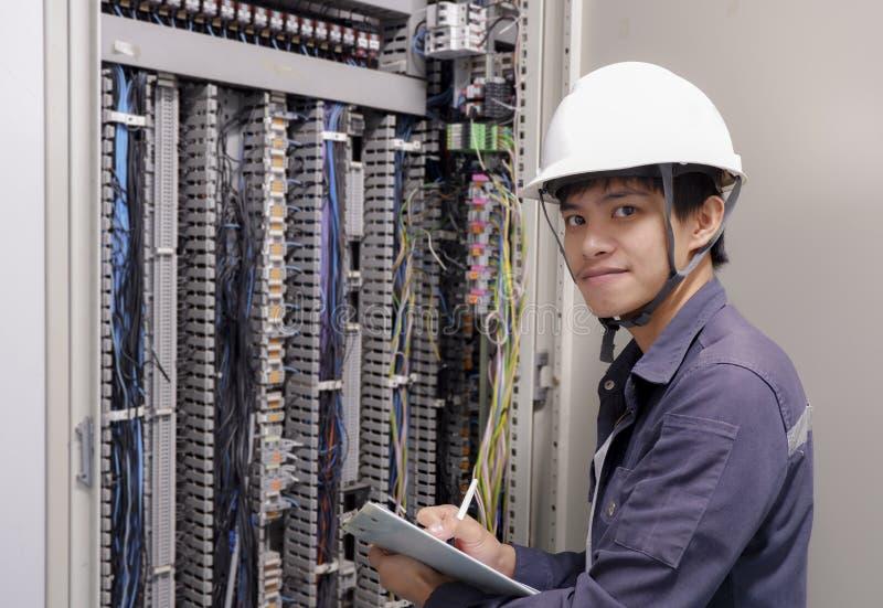 Électriciens souriant, inspectant les boîtes électriques dans l'usine industrielle photographie stock libre de droits