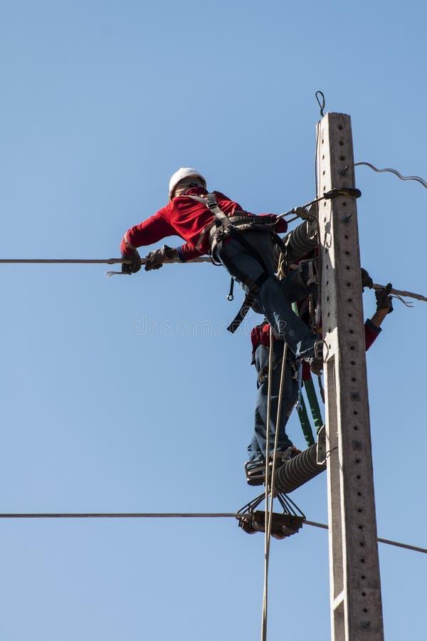 Électriciens travaillant à un pylône photographie stock libre de droits