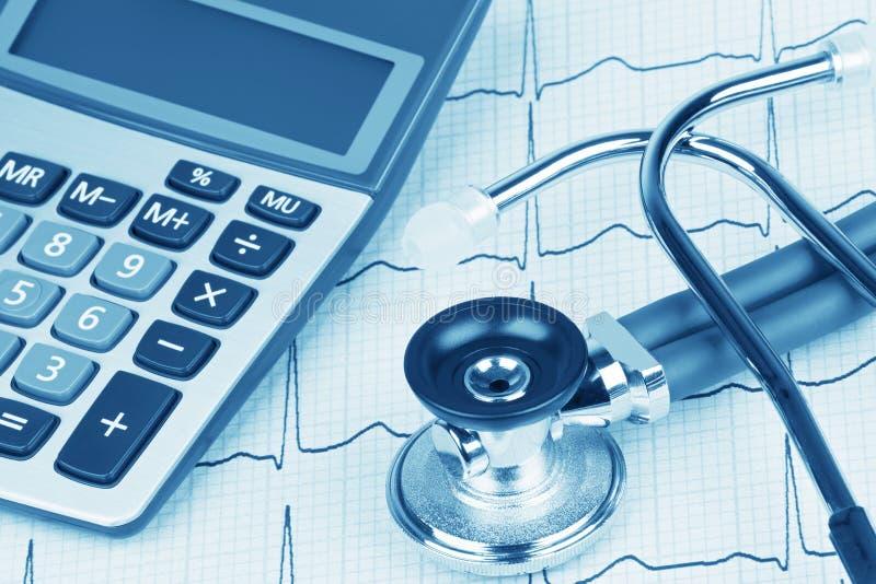 électrocardiogramme avec le stéthoscope et la calculatrice montrant le coût de soins de santé photos libres de droits