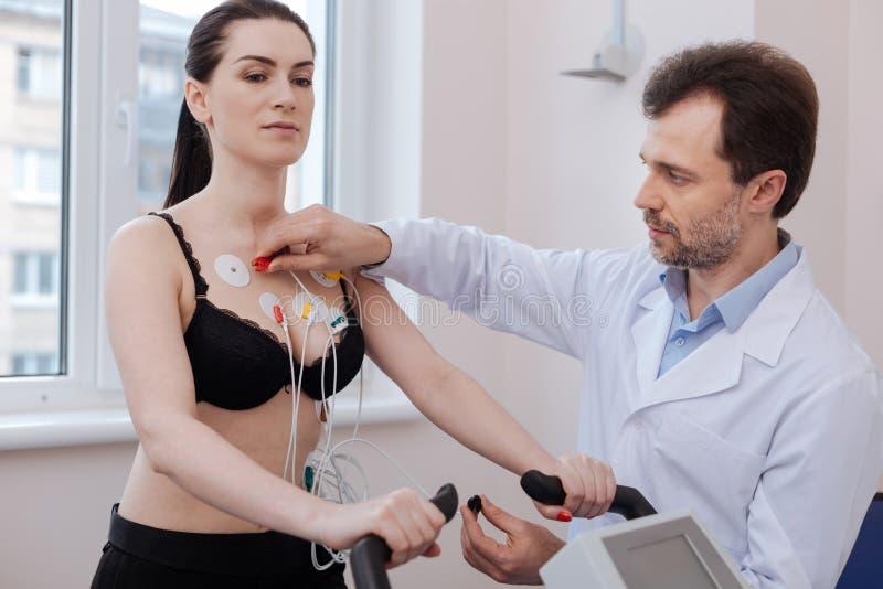 Électrodes se reliantes qualifiées focalisées de cardiologue photographie stock libre de droits