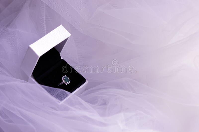 Émeraude d'or blanc et bague de fiançailles uniques de diamant dans la boîte image stock